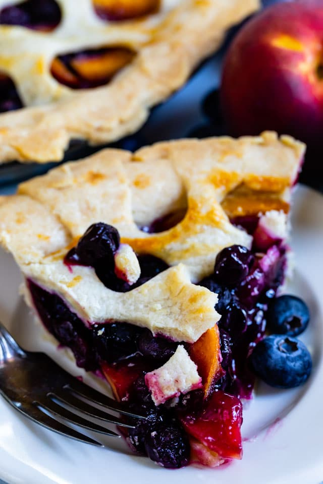 Close up shot of peach blueberry pie slice on a white plate
