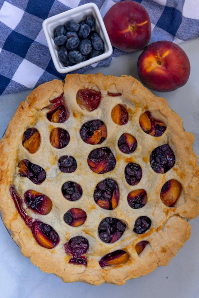 Overhead shot of peach blueberry pie on kitchen counter with fresh peaches and blueberries next to it