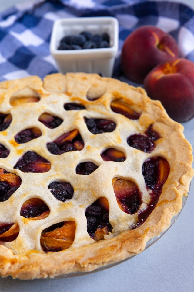 Close up shot of peach blueberry pie in a pie dish with fresh fruit behind it