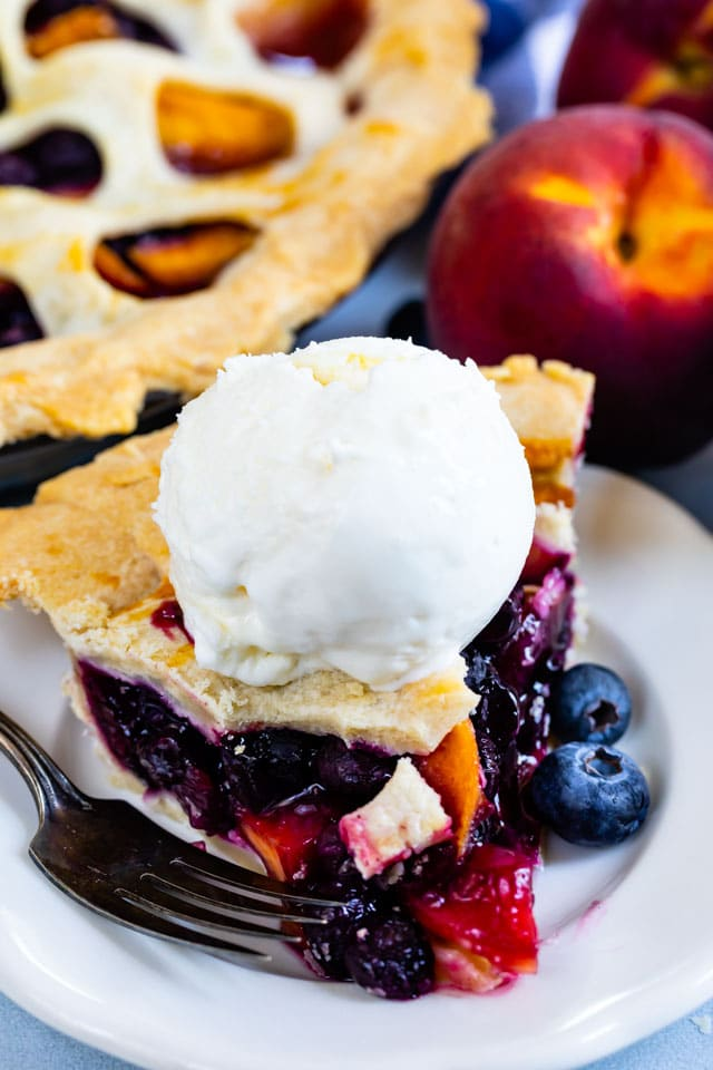 Slice of peach blueberry pie on a white plate with a scoop of vanilla ice cream on top
