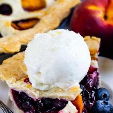 Slice of peach blueberry pie on a white plate with a scoop of vanilla ice cream on top and recipe title on top of image