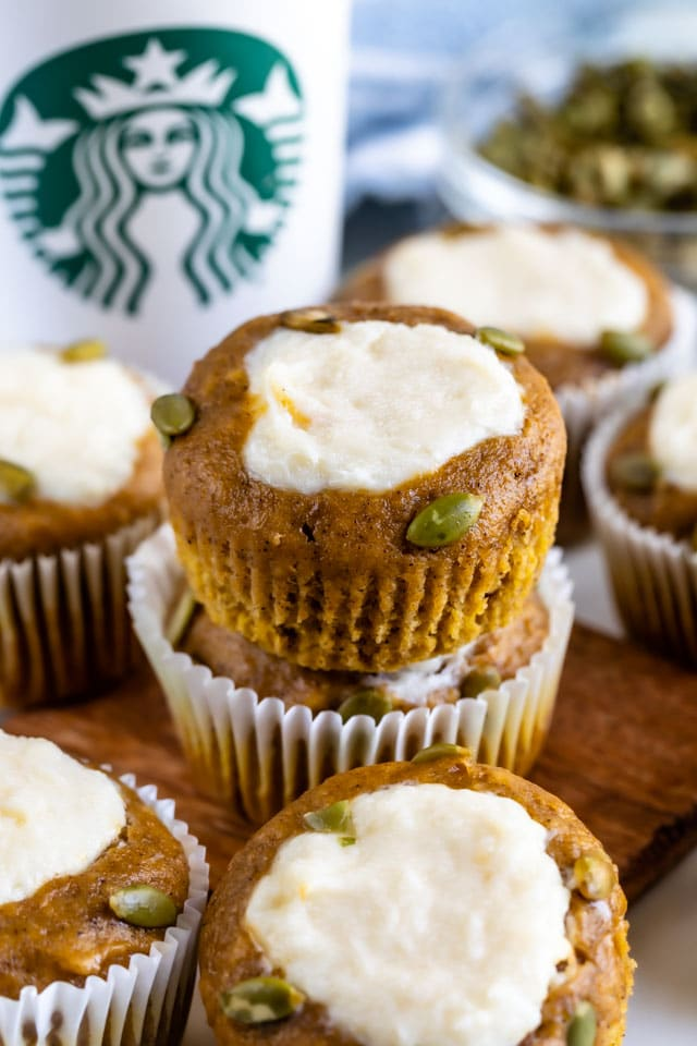 Copycat pumpkin cream cheese muffins on a wood cutting board with Starbucks cup in background
