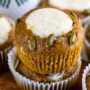 Close up of pumpkin cream cheese muffins stacked on top of eachother