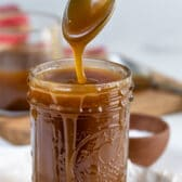 Spoonful of salted caramel sauce coming out of mason jar