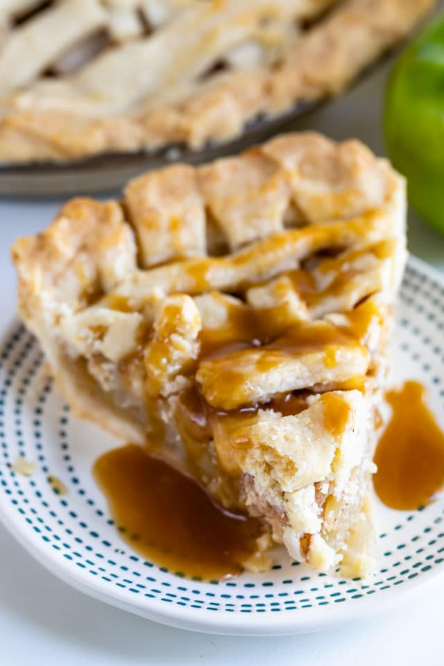 Salted caramel apple pie slice on a blue dotted plate with salted caramel sauce on top