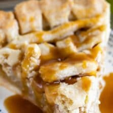Salted caramel apple pie slice on a blue dotted plate with salted caramel sauce on top with recipe title on top