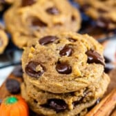 Stack of pumpkin chocolate chip cookies with ingredients around them and more cookies in background