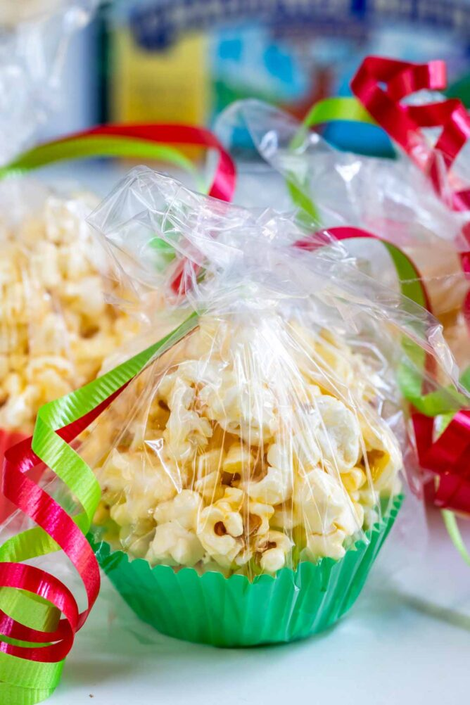 popcorn in green muffin liner wrapped in plastic with christmas colored ribbon