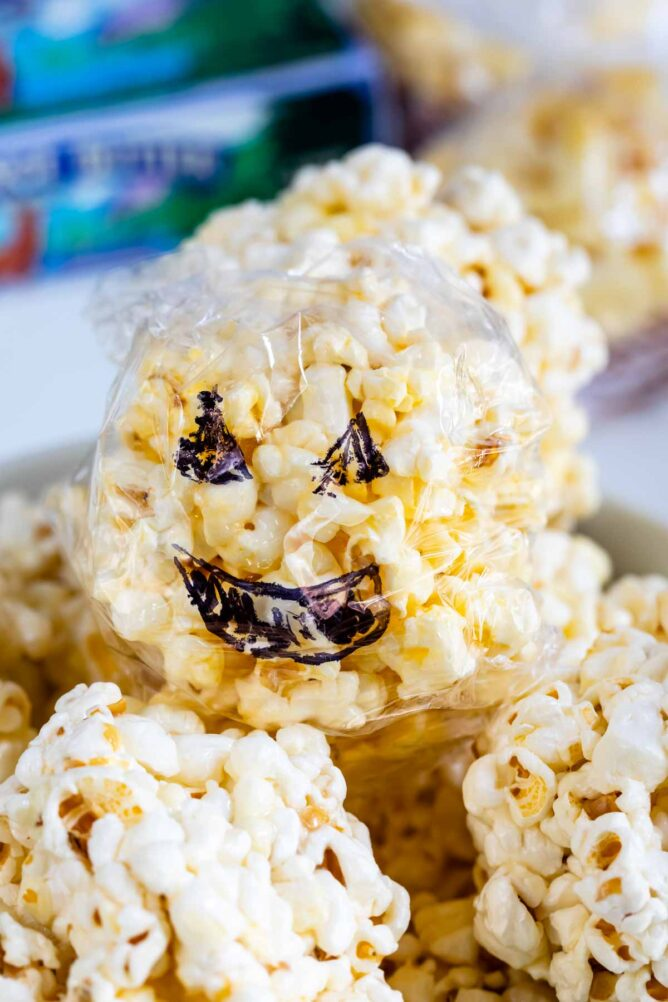 popcorn ball covered in plastic with jack o' lantern design