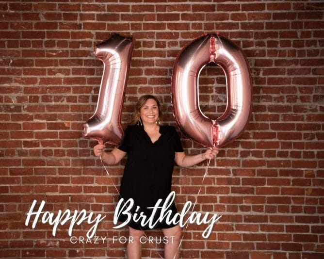 woman in front of brick wall holding 10 balloons