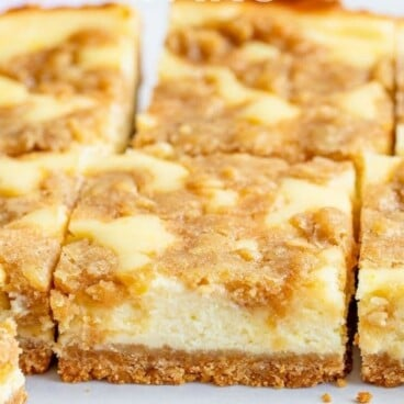 Lemon cheesecake bars on counter cut into squares with recipe title on top of image