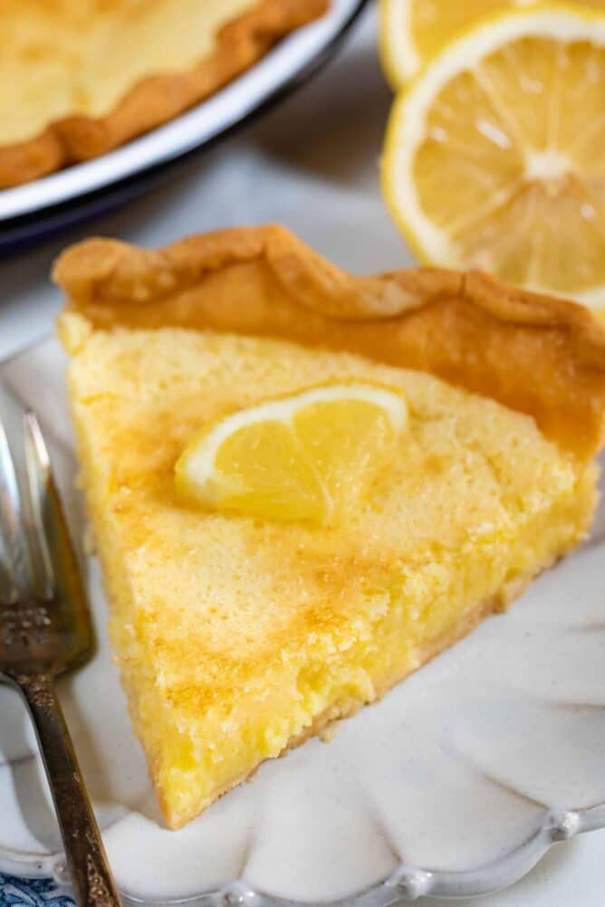 Close up photo of slice of lemon chess pie on a white scalloped plate