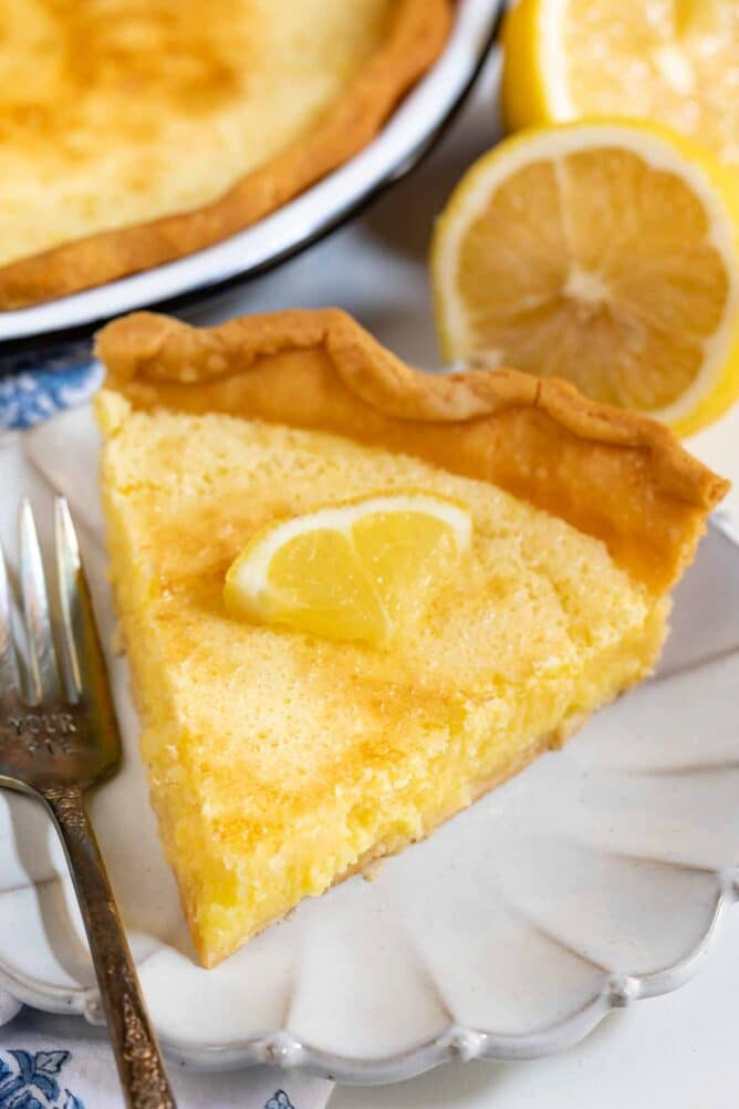Slice of lemon chess pie on a scalloped plate with silver fork