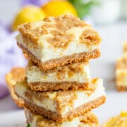 Stack of lemon cheesecake bars on counter with lemon slices and mint leaves on counter