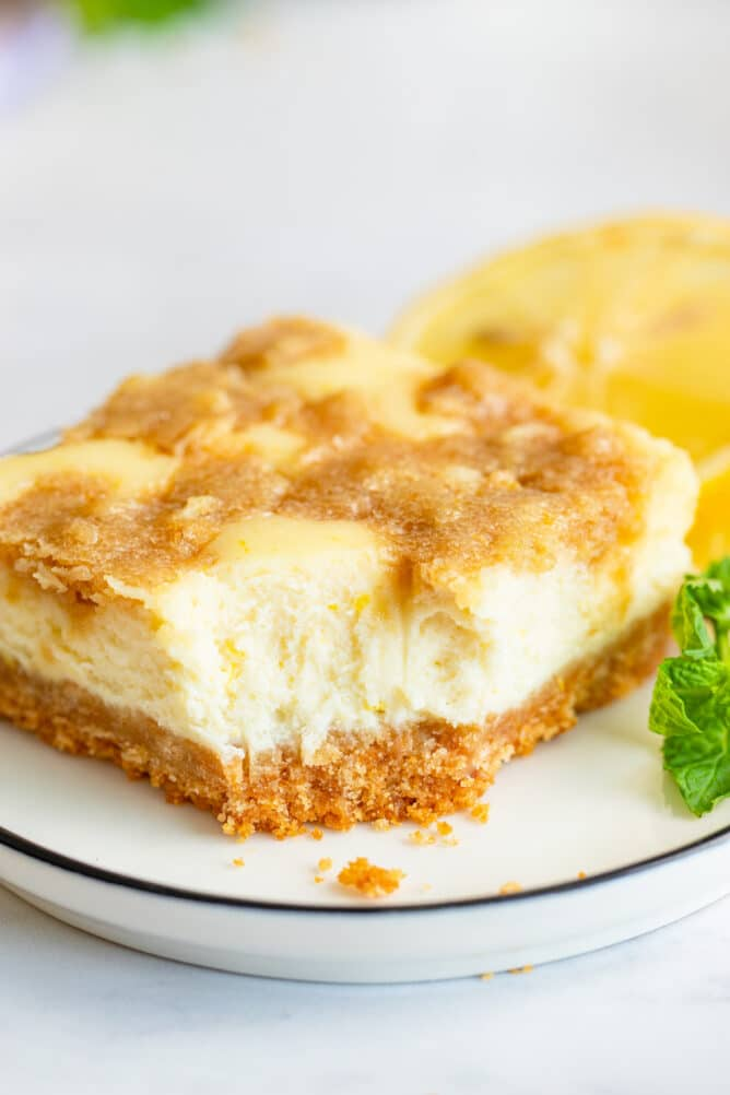 Lemon cheesecake bar on a plate with one bite missing from corner