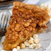 One slice of macadamia nut pie on a white scalloped plate with extra white chocolate chips and macadamia nuts