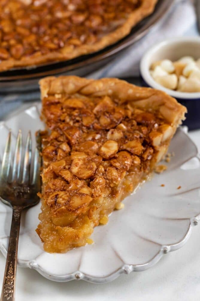Slice of macadamia nut pie on a white scalloped plate with silver fork
