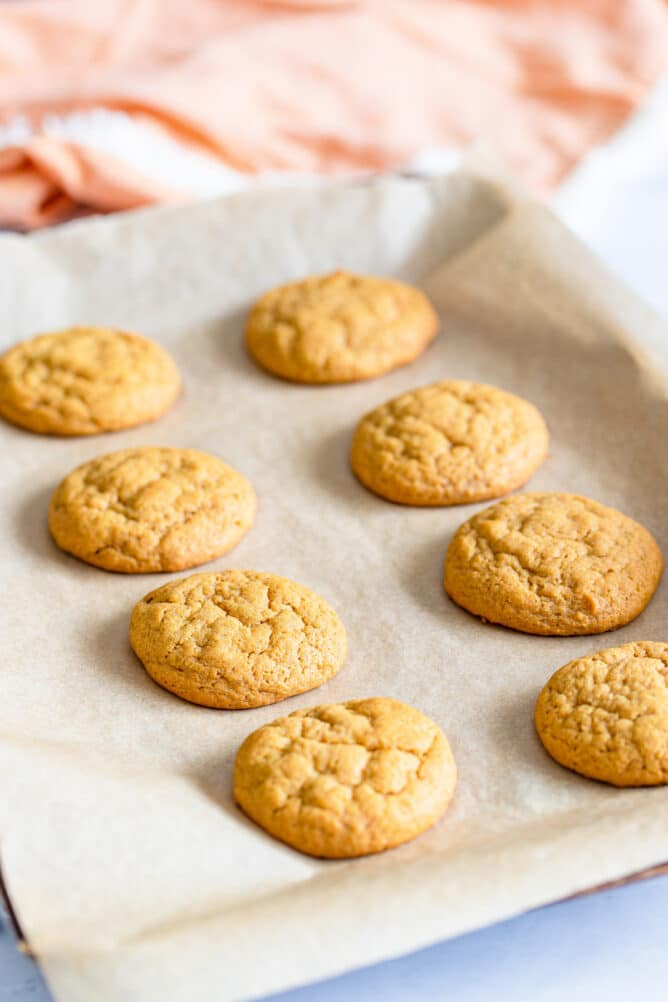 Pumpkin cookies on a sheet pan with parchment paper after being baked