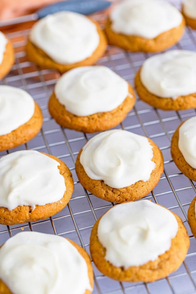 Overhead shot of pumpkin cookies with cream cheese frosting on a wire drying rack