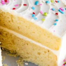 Layered yellow cake with vanilla frosting and rainbow sprinkles with slice cut out and recipe title on image