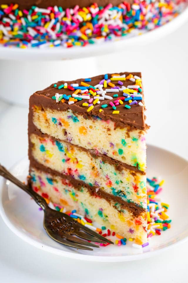 One slice of layered funfetti birthday cake with chocolate frosting and rainbow sprinkles on a white plate with fork