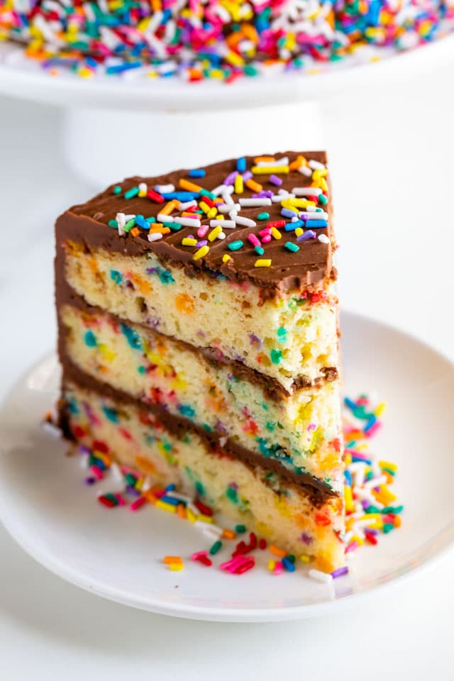 One slice of layered funfetti birthday cake with chocolate frosting and rainbow sprinkles on a white plate with one bite missing