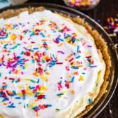Overhead shot of funfetti pie with rainbow sprinkles on wood table