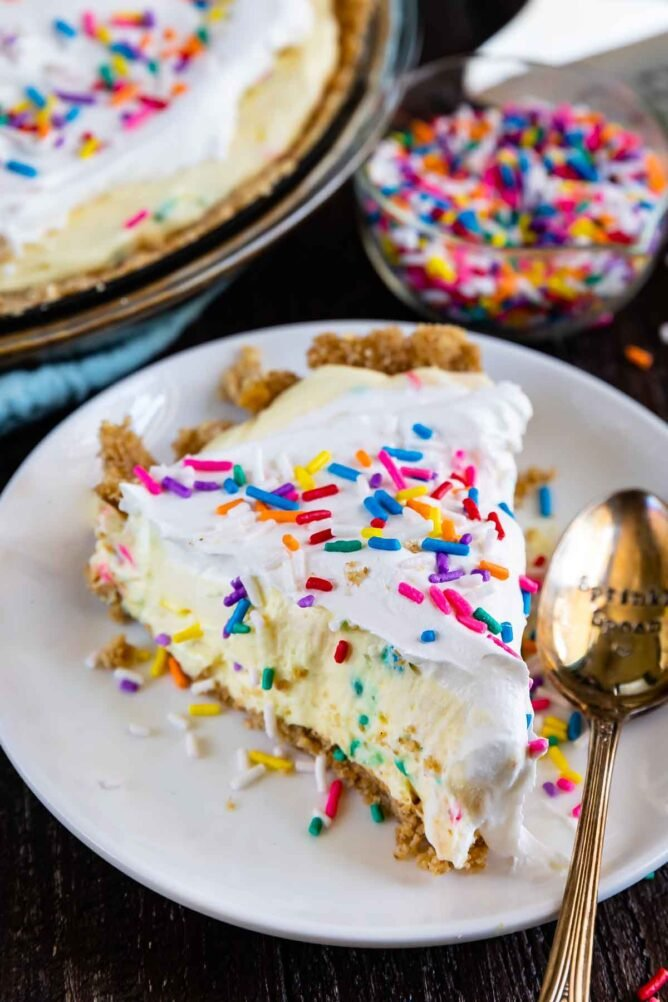 Slice of funfetti pie on a white plate with silver spoon and sprinkles in the background