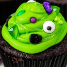 chocolate cupcake with green frosting with spooky sprinkles to look like cauldrons