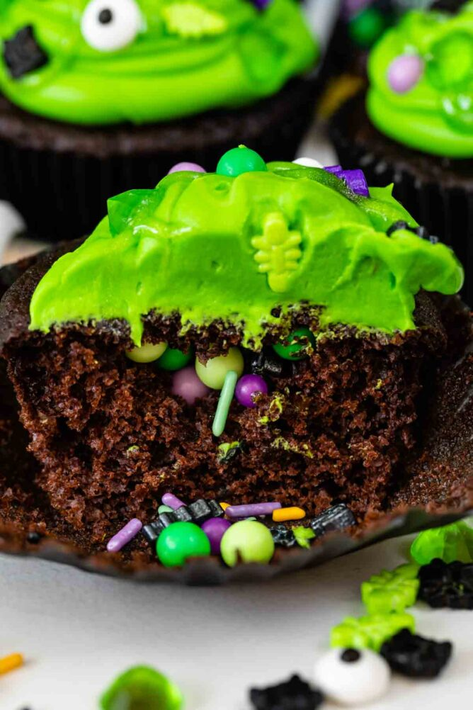 chocolate cupcake with green frosting cut open to show sprinkles inside