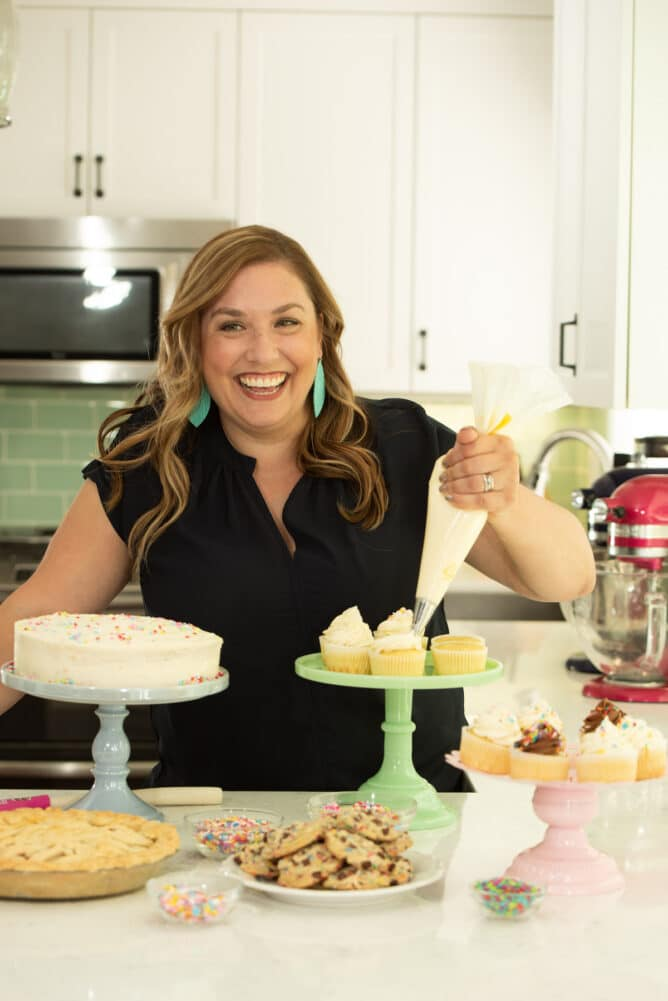 woman holding piping bag frosting cupcakes with desserts in front of her