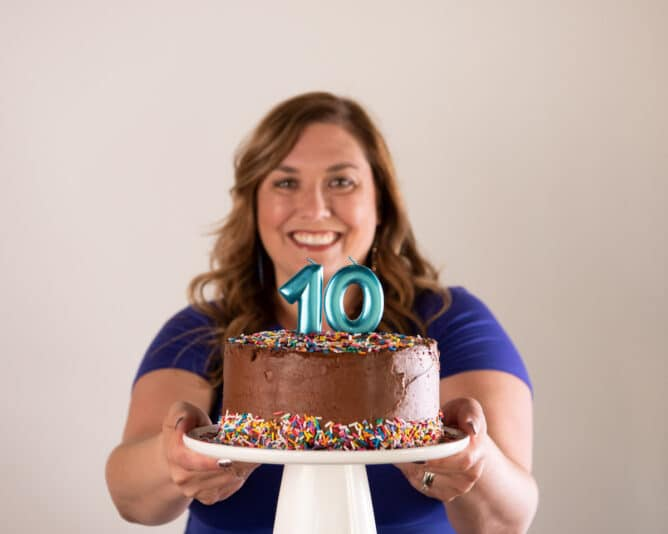 woman holding chocolate birthday cake with teal number 10 candles on white cake plate