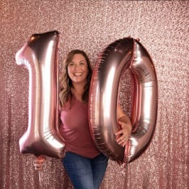 woman in pink shirt holding pink number balloons 10 with pink backdrop