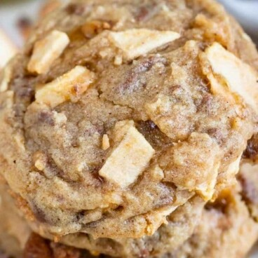 Close up photo of stack of apple cookies with toffee bits all around and recipe title on top of photo