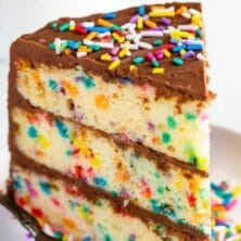 One slice of layered funfetti birthday cake with chocolate frosting and rainbow sprinkles on a white plate with fork and recipe title on image