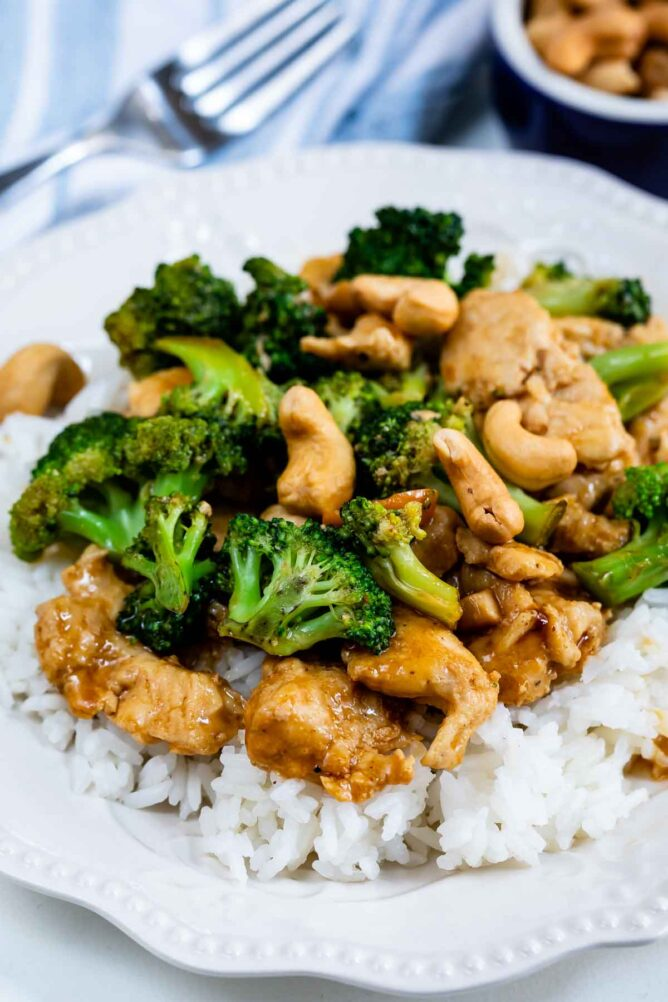 cashew chicken stir fry on bed of white rice on white plate