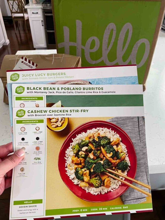 hand holding 3 hello fresh meal kit instruction flyers