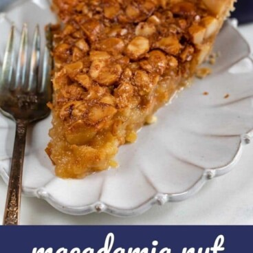 Slice of macadamia nut pie on a white scalloped plate with silver fork and recipe title on bottom of image