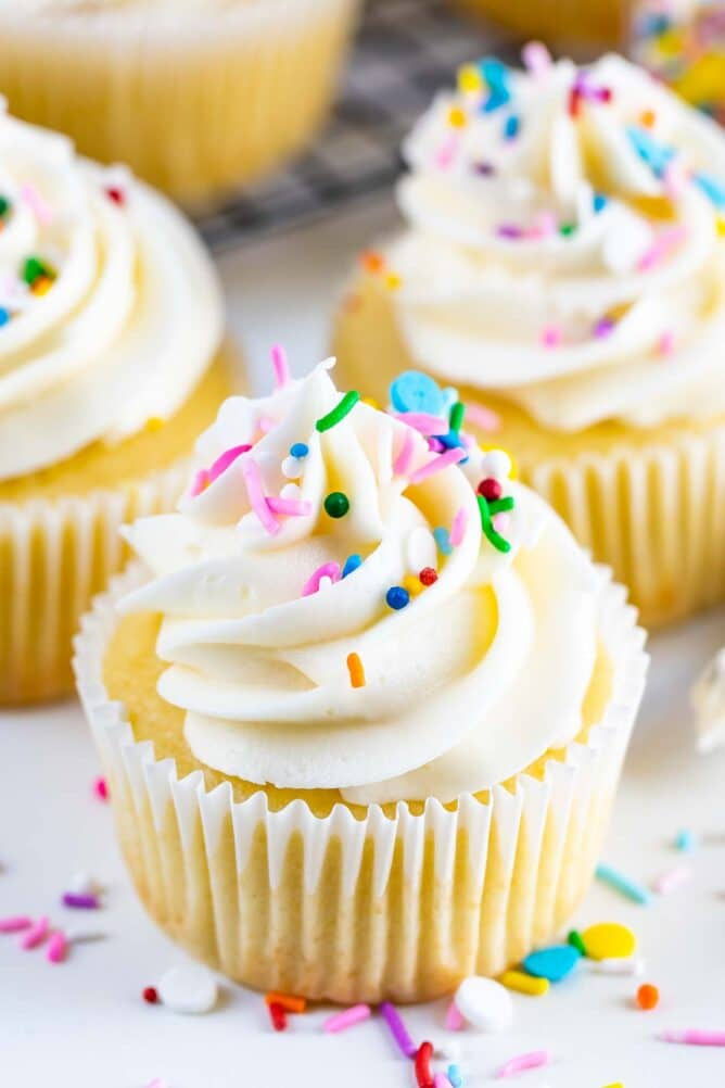 Yellow cake cupcakes with vanilla frosting and sprinkles on top and around bottom