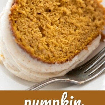 One slice of pumpkin bundt cake on a white plate with silver fork with recipe title on bottom of image
