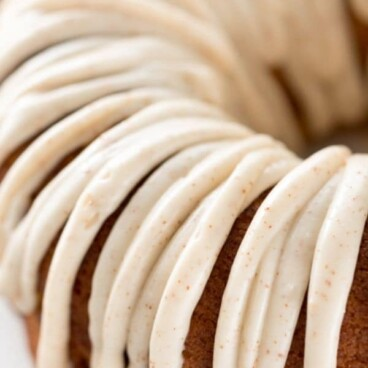 Overhead shot of half of the pumpkin bundt cake with ribbon like frosting and recipe title on top of image