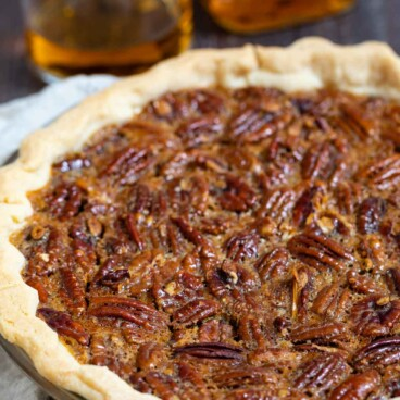 Bourbon pecan pie in pie dish with bourbon bottle and glass behind pie