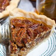 One slice of bourbon pecan pie on a white plate with blue dotted border and silver fork