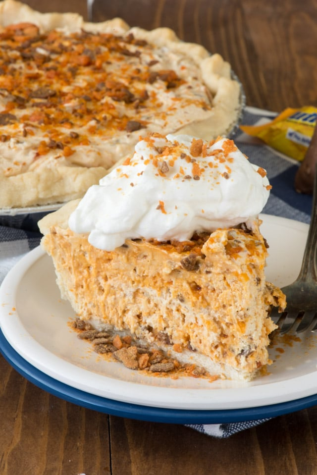 Slice of butterfinger pie on a white and blue plate with rest of pie in background
