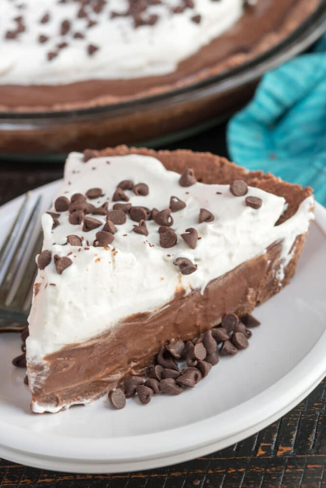 slice of chocolate pie with whipped cream on white plate
