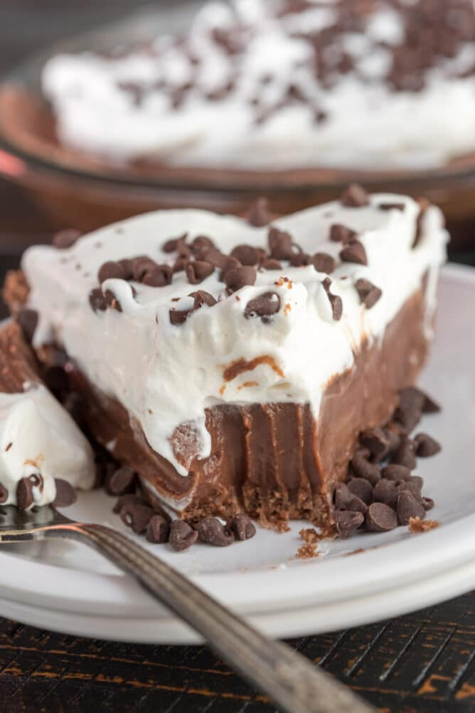 slice of chocolate pie with whipped cream on white plate with bite missing