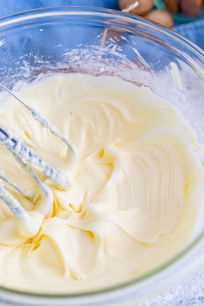 Overhead shot of eggnog frosting being whisked in clear mixing bowl