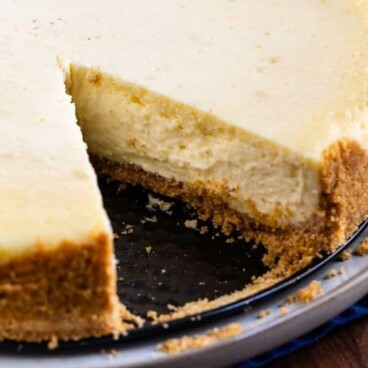 Overhead shot of classic cheesecake with one slice missing and recipe title on bottom of image