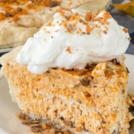 Slice of butterfinger pie on a white and blue plate with rest of pie in background and recipe title on top of image