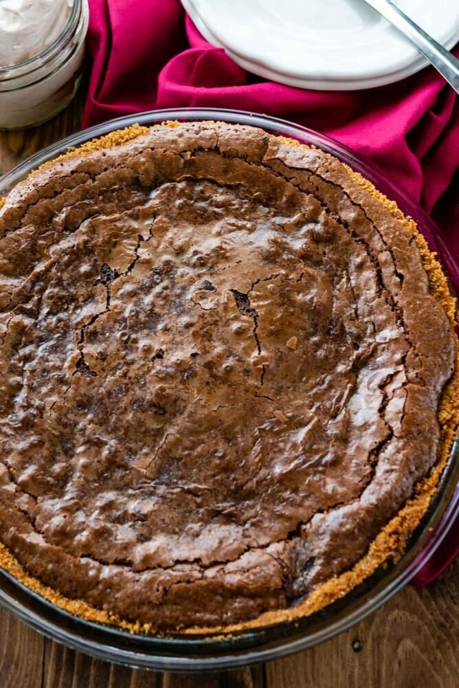 overhead of chocolate pie in graham cracker crust with pink napkin